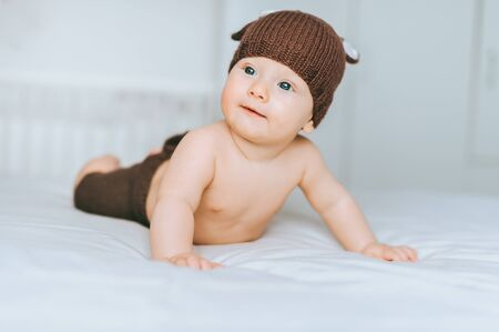 smiling infant child in beautiful knitted deer costume in bed