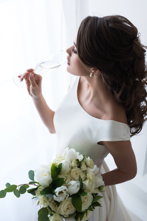 beautiful young bride with wedding bouquet drinking champagne