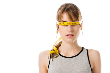 young slim woman with measuring tape tied around her eyes isolated on white Stock Photo