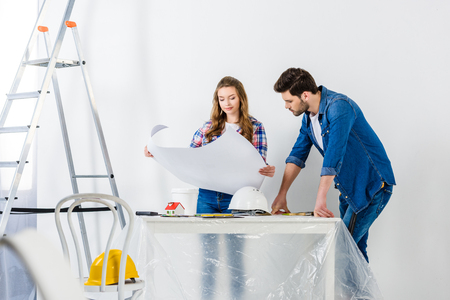 couple looking at blueprint during home repairs 写真素材