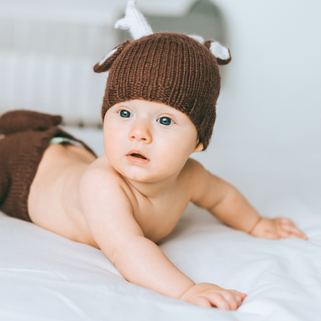 close-up portrait of adorable infant child in knitted deer costume in bed