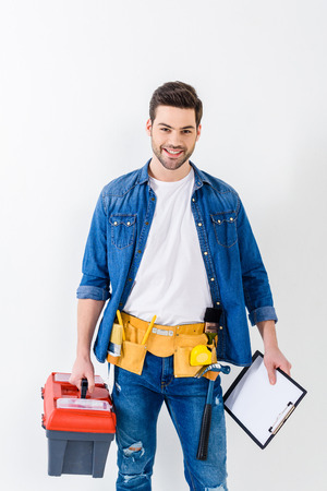 smiling handsome worker with tools box and clipboard