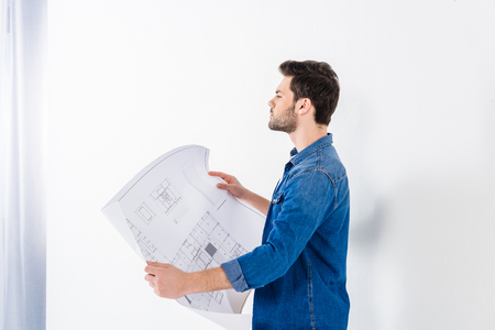 handsome architect holding blueprint and looking away