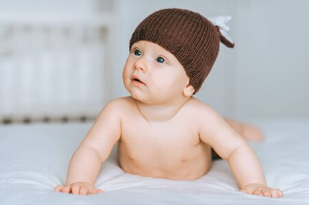 adorable infant child in knitted deer hat in bed
