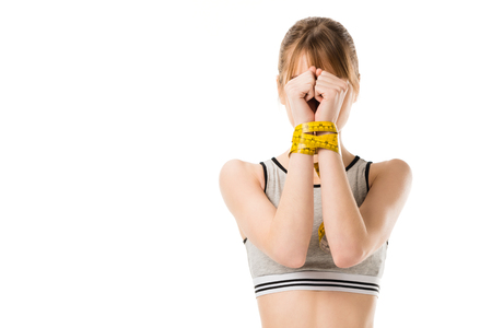 attractive slim woman covering face with hands tied in measuring tape isolated on white 스톡 콘텐츠