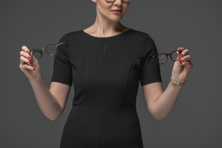 cropped shot of woman in black dress choosing eyeglasses isolated on grey Stok Fotoğraf