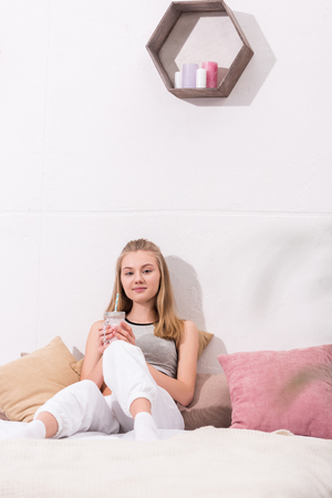 happy young woman drinking milkshake while sitting on bed Stock fotó