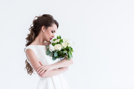 beautiful bride sniffing wedding bouquet, isolated on white