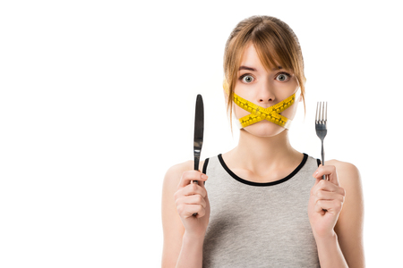 shocked young woman with measuring tape tied around her mouth holding fork and knife isolated on white Stok Fotoğraf - 114259926