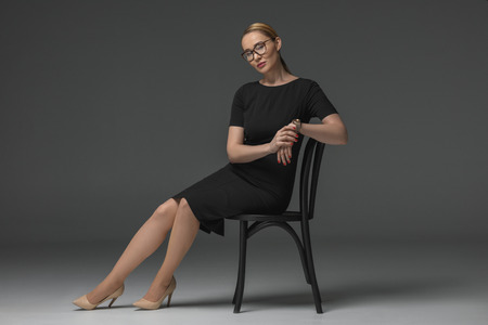 full length view of beautiful kazakh woman in eyeglasses and black dress sitting on chair on grey