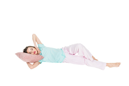 young woman in pajamas lying on pillow with closed eyes isolated on white Stock fotó