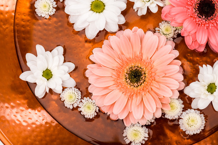top view of daisies and gerbera flowers in metalic plate for spa procedure