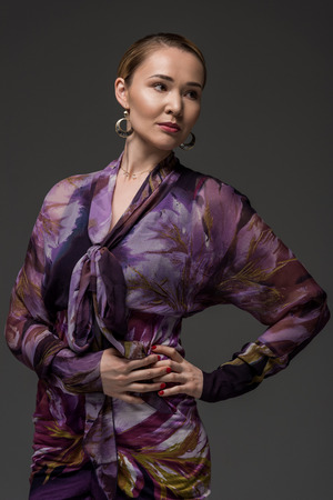 portrait of elegant kazakh woman posing with hands on waist and looking away isolated on grey Stok Fotoğraf