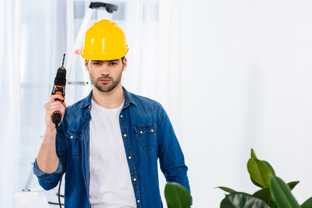 handsome man standing with drill and looking at camera