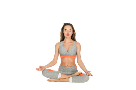 young woman with closed eyes meditating in lotus position isolated on white