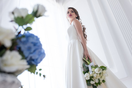 bottom view of bride posing in white dress with wedding bouquet