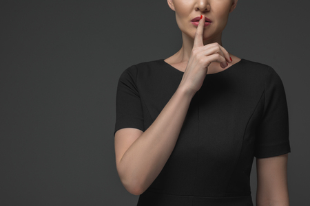 cropped shot of kazakh woman gesturing for silence isolated on grey Stock Photo