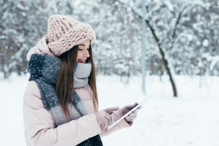 side view of smiling young woman with tablet in winter park