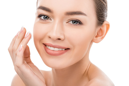 beautiful smiling girl with clean face applying cosmetic cream, isolated on white