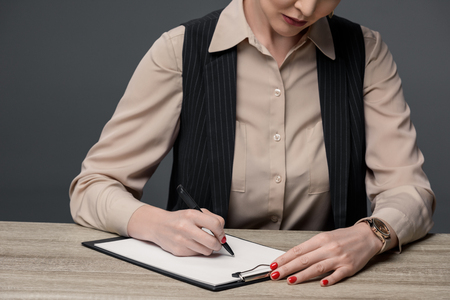 cropped shot of kazakh businesswoman writing on clipboard at table isolated on grey Stok Fotoğraf - 114264141