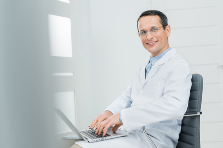 Doctor working by laptop in modern clinic Stock Photo