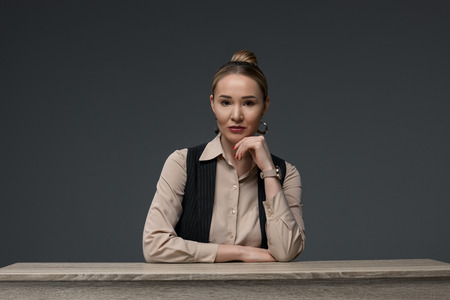 beautiful kazakh businesswoman sitting at table and looking at camera isolated on grey Stok Fotoğraf