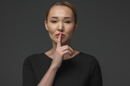 beautiful kazakh woman gesturing for silence isolated on grey