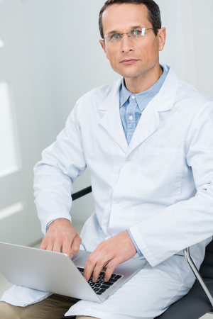 Doctor working by laptop in modern  clinic