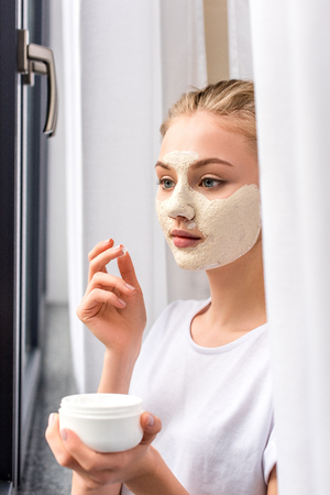 attractive young woman applying white clay mask on face at home