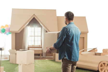 man with boxes moving into new cardboard house isolated on white Imagens