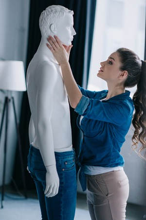 side view of young woman and mannequin at home, one way love concept