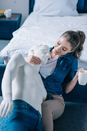 smiling woman with cup of coffee hugging layman doll, perfect relationship dream concept