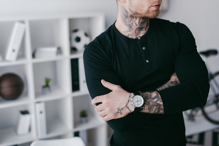 cropped shot of young businessman with tattoos standing with crossed arms in office