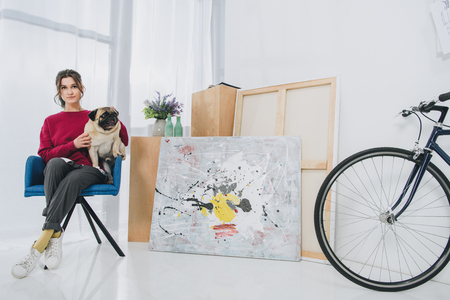 Young woman cuddling pug in chair in modern room Stock fotó