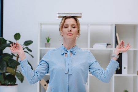 attractive businesswoman meditating with book on head at office Stock Photo
