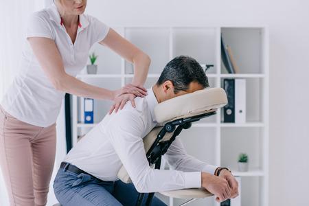beautiful adult masseuse doing seated massage for businessman