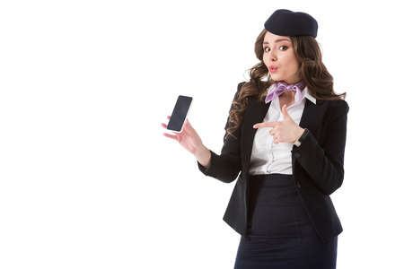 attractive stewardess pointing on smartphone isolated on white