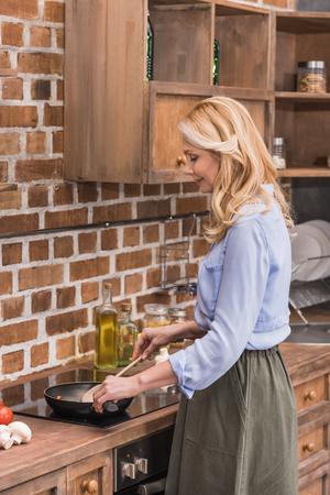 attractive woman stirring vegetables on frying pan Reklamní fotografie