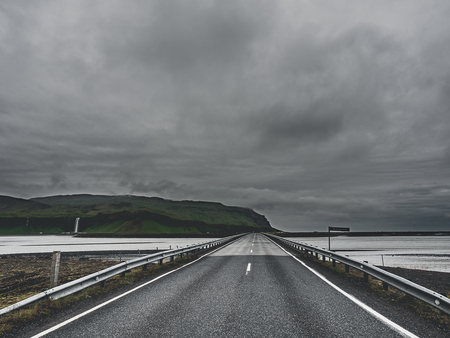 road and bridge over the river at cloudy day in Iceland