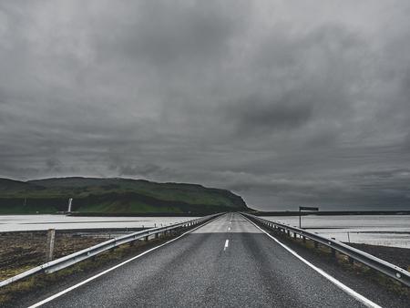 Straße und Brücke über den Fluss am bewölkten Tag in Island Standard-Bild