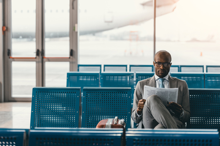 serious businessman reading newspaper waiting for flight at airport lobby