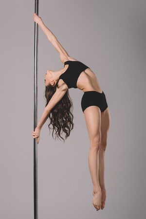 full length view of attractive flexible girl dancing with pole on grey