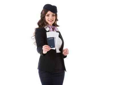 attractive stewardess showing passport and tickets isolated on white Foto de archivo