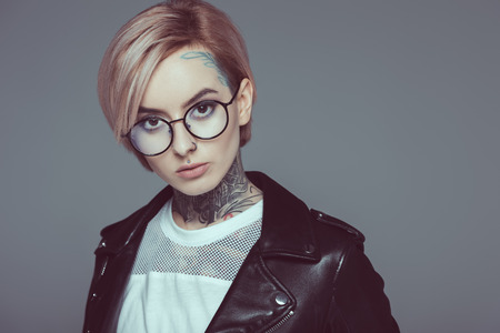 tattooed girl with pink hair in eyeglasses and black leather jacket, isolated on grey