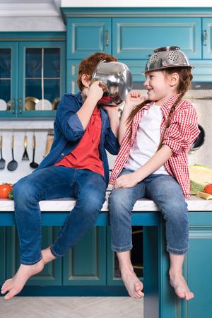 schattige kinderen op blote voeten die plezier hebben met keukengerei terwijl ze op de keukentafel zitten