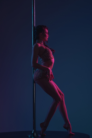 side view of seductive young woman leaning at pole and looking away on blue Standard-Bild