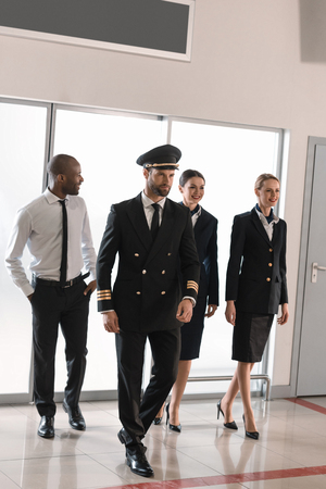 happy aviation personnel team in professional uniform walking by airport Stockfoto