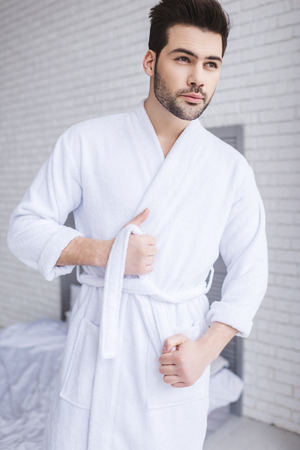 handsome young man tying belt of bathrobe and looking away at home