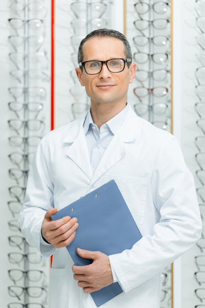 portrait of optometrist with notepad in hands looking at camera in optics