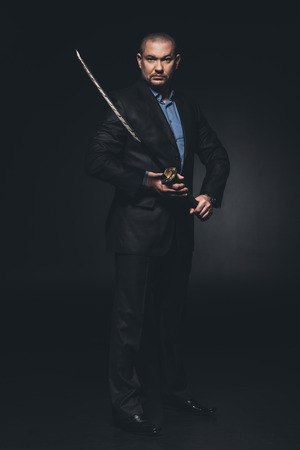 mature man in suit with japanese katana sword on black 写真素材